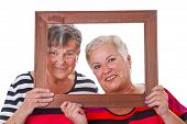 Two Senior Women Looking Through A Picture Frame