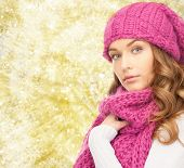 happiness, winter holidays, christmas and people concept - young woman in pink hat and scarf over yellow lights background