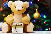 Teddy bear and gift box on Christmas tree background