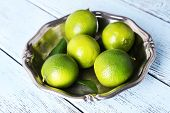 Fresh juicy limes on plate on wooden background