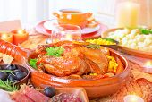 Traditional Thanksgiving family dinner with tasty grilled turkey in centerpiece of festive table, many delicious food for traditional autumn holiday