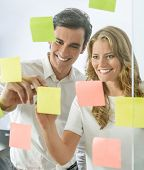 Male and female coworkers standing in front of a glass wall with sticky notes