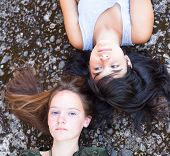 Two teenage girl friends lying on a granite background, top view close-up.