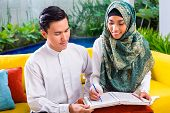 Asian Muslim man teaching woman reading Koran or Quran in living room