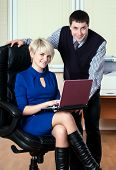 Young attractive business people work with laptop