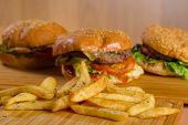 Potatoes fries with tasty fresh burgers standing on wooden board