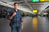 Young backpacker with a backpack in an international airport on his way to the gate