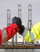 Handshake between two people in work clothing, symbolizing a lucrative deal for in- or export against three harbor cranes
