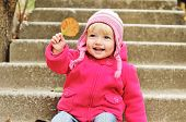 picture of dimples  - toddler girl with leaf on the stairs - JPG
