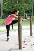 Sporty woman stretching inside of thigh on a bar, exercising in the park