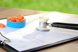 image of lobbyist  - orange pills prescription and phonendoscop on a green background - JPG