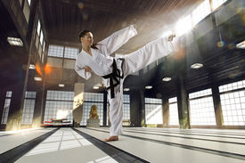 stock photo of karate-do  - Karate woman in action on light old sports hall - JPG