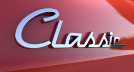 stock photo of emblem  - A closeup view of the word classic writting as a chrome emblem in a retro font set on a car painted in reflective red paint - JPG