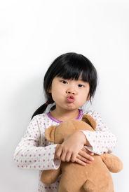 stock photo of goodnight  - Little child in pyjamas holding teddy bear - JPG