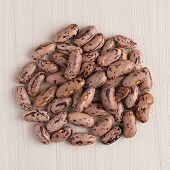 pic of pinto bean  - Top view of circle of pinto beans against beige vinyl background - JPG