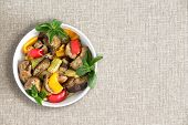 image of brinjal  - Plate of delicious grilled fresh vegetables prepared Turkish style with eggplant zucchini and red and yellow sweet peppers over head view on a beige cloth with copyspace - JPG