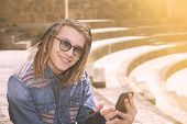 picture of dreadlocks  - freelancer guy with dreadlocks sitting on staircase with digital tablet typing message warm filter applied - JPG