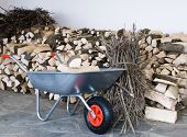 stock photo of wheelbarrow  - The wheelbarrow full of wood - JPG