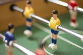 stock photo of movable  - Retro toy football or soccer player suspended on a movable metal rod in a vintage board game selective focus to one player