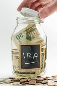 picture of raid  - Hand opening lid of glass jar on white background with black chalk label and used for savings US dollar bills for IRA and retirement - JPG