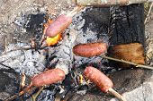 image of ember  - Grilling sausages on the embers of a campfire
