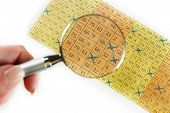 image of lottery winners  - Female hand with magnifier analyzing lottery ticket - JPG