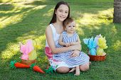 image of baby easter  - Smiling beautiful teen girl holding sister - little baby girl on green grass in park with wicker basket with chocolate eggs for Easter. Selective focus