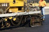 foto of paving  - Asphalt paving machine laying down a fresh layer of paving on a new road interchange project - JPG