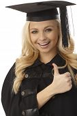 stock photo of convocation  - Closeup photo of happy blonde female graduate showing thumb - JPG