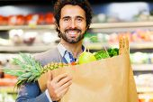 stock photo of supermarket  - Man shopping in a supermarket - JPG