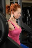 stock photo of squatting  - young red haired girl doing squats with barbell on smith machine - JPG