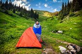 image of sleeping bag  - Tourist in sleeping bag near orange tent in the mountains in Kazakhstan central Asia - JPG