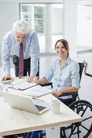 image of wheelchair  - Confident business woman in wheelchair working at office desk with her male colleague and smiling at camera - JPG