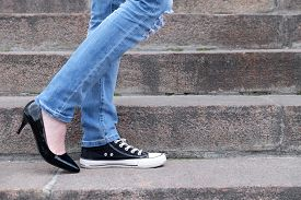 stock photo of street-walker  - Female feet in different shoes on  stone stairs - JPG