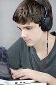 Teen Wearing Headphones Works On Computer