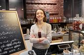 small business, people and service concept - happy woman or barmaid at counter with cashbox in cafe  poster