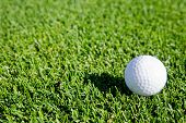 A golf ball sitting on green grass - background image