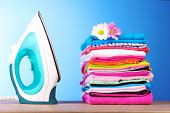 Pile of colorful clothes and electric iron  on blue background