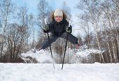 Young boy with cross-country skis and poles jumps and tongue out inside winter forest at sunny day