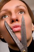 stock photo of fat lip  - Beautiful young woman pretending to cut her lips with scissors - JPG