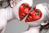 Two pretty girls with faces painted red heart shapes