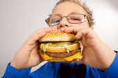 image of junk food  - Young fat school boy eating hamburger - JPG