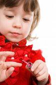 Chica bonita en rojo aplicar esmalte de uñas