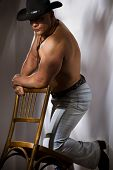 Muscular shirtless cowboy leaning on chair against a white wall