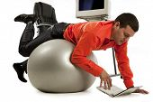 Young businessman doing push-ups and looking on laptop screen.