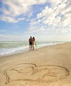 Hearts drawn on the sand of a beach (foreground), the man and woman on the background