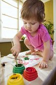 Beautiful baby girl sitting on the table covered in bright paint and painting with finger paints and with paint brush