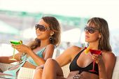 Two beautyful  women enjoying their summer vacation with a glasses of martini