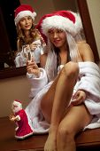 stock photo of promiscuous  - Portrait of two sexy girls in Santa hats with the glasses of champagne waiting for New Year - JPG