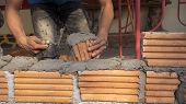 Bricklayer Worker Installing Brick Masonry On Exterior Wall poster